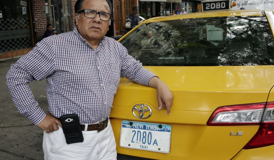 In this June 26, 2017 photo, taxi driver and taxi medallion owner Marcelino Hervias poses for photos with his taxicab on New York's Upper West Side. Just three years ago, cab owners and investors were paying as much as $1.3 million for a medallion. Now they are worth less than half that amount. (AP Photo/Richard Drew)
