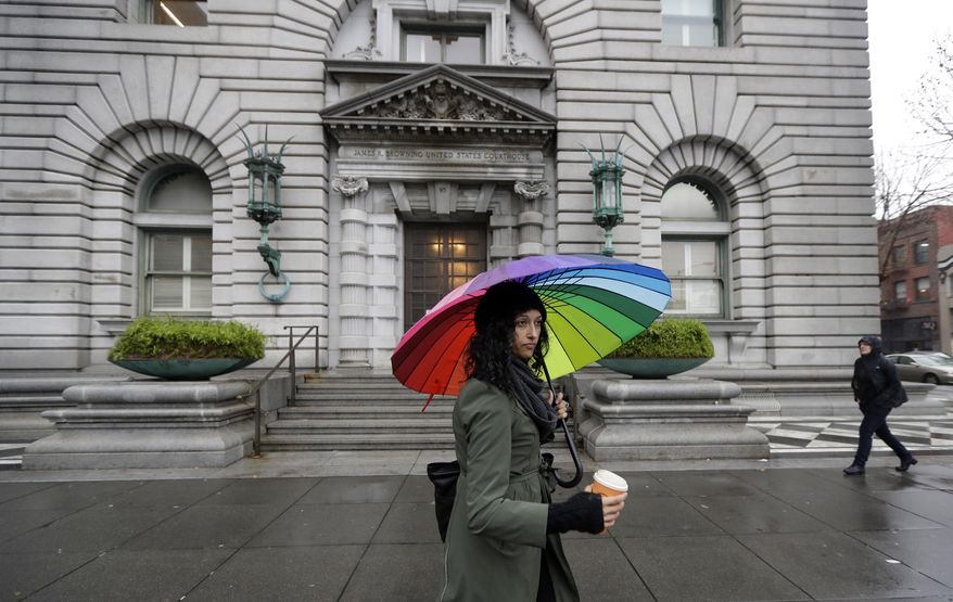 FILE - In this Feb. 9, 2017, file photo, Monica Fine, center, walks past the 9th U.S. Circuit Court of Appeals building in San Francisco. The nation's largest federal court circuit is set for its annual meeting after a contentious six months that has seen its judges repeatedly clash with President Donald Trump, and its agenda is not shying away from topics that have stoked the president's ire. Immigration, the news media and meddling in the U.S. election are among the subjects that will be discussed at the 9th Circuit's four-day conference in San Francisco that begins on Monday, July 17, 2017. (AP Photo/Marcio Jose Sanchez, File)