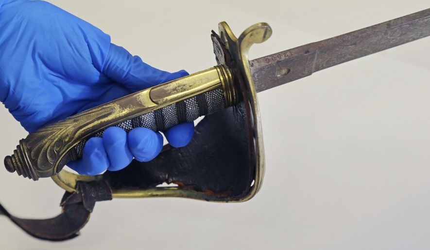 In this July 14, 2017 photo taken at the Massachusetts Historical Society in Boston, the sword that belonged to Col. Robert Gould Shaw, the commanding officer of the first all-black regiment raised in the North during the Civil War is held. The sword, stolen after Shaw was killed during the 54th Massachusetts Voluntary Infantry's attack on Fort Wagner, South Carolina in 1863, was recently found in the attic of a Boston-area home. (AP Photo/Elise Amendola)