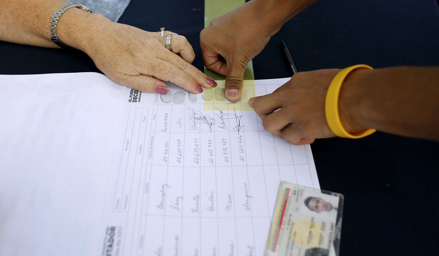 Venezuelans voters will use special government-issued ID cards that have two numbers on the back. Plugged into the electoral system database, the numbers generate the identities of two people. (Associated Press/File)
