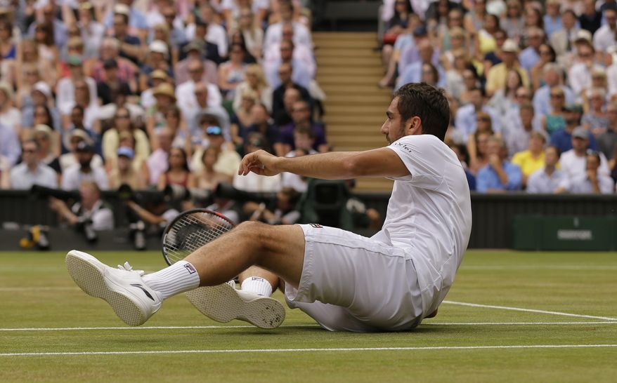 Croatia's Marin Cilic takes a tumble after returning to Switzerland's Roger Federer in the Men's Singles final match on day thirteen at the Wimbledon Tennis Championships in London Sunday, July 16, 2017.. (AP Photo/Alastair Grant)