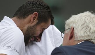 Croatia's Marin Cilic has treatment on his foot as he takes a medical timeout during the Men's Singles final match against Switzerland's Roger Federer on day thirteen at the Wimbledon Tennis Championships in London Sunday, July 16, 2017. (Daniel Leal-Olivas/Pool Photo via AP)