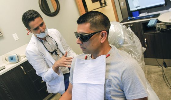 ADVANCE FOR SUNDAY JULY 16 AND THEREAFTER - In a Wednesday, June 21, 2017 photo, dentist Antonio Lopez-Ibarra, left, speaks to his patient, Jonathan Martinez, 34, of Pasco, inside Tri-City Dental in Kennewick, Wa., before examining him. Lopez-Ibarra is one of a growing number offering spa-like services to patients. The extras _ from paraffin hand wax to aromatherapy _ help calm patients, make treatments go more smoothly and contribute to a better overall experience, Lopez-Ibarra and others said. (Noelle Haro-Gomez/The Tri-City Herald via AP)