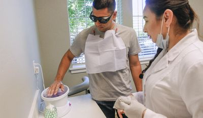 ADVANCE FOR SUNDAY JULY 16 AND THEREAFTER - In a Wednesday, June 21, 2017 photo, Jonathan Martinez, 34, of Pasco, dips his hands into parafin wax as Julia Vargas, a dental assistant, waits to put gloves on Martinez at Tri-City Dental in Kennewick, Wa.  A growing number of dentists are offering spa-like services to patients. The extras _ from paraffin hand wax to aromatherapy _ help calm patients, make treatments go more smoothly and contribute to a better overall experience, Lopez-Ibarra and others said. (Noelle Haro-Gomez/The Tri-City Herald via AP)