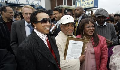 FILE - In this Friday, Oct. 19, 2007 file photo, Berry Gordy Jr., center, stands with Smokey Robinson, left, and Detroit Councilwoman Martha Reeves outside Hitsville U.S.A. and the Motown Museum in Detroit. Gordy was honored with the renaming of the street where the Motown sound originated. Motown was near the epicenter of the 1967 riots but largely spared during unrest that enveloped 25 city blocks and claimed 43 lives. (AP Photo/Carlos Osorio)
