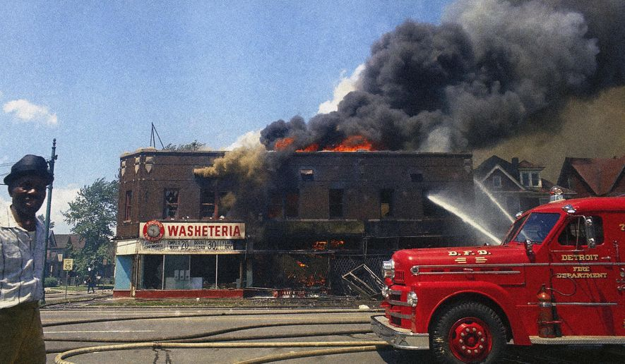 FILE - In this July 1967 file photo, firefighters spray water into a burning building after rioting in Detroit. (AP Photo)