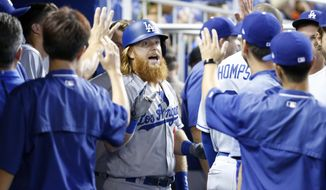 Los Angeles Dodgers' Justin Turner, center, celebrates with teammates after hitting a home run during the first inning of a baseball game against the Miami Marlins, Sunday, July 16, 2017, in Miami. (AP Photo/Wilfredo Lee)