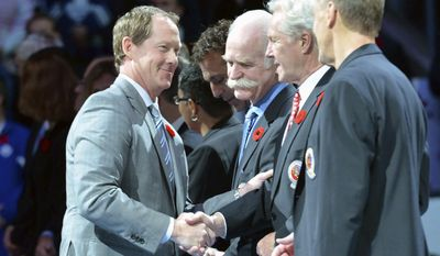FILE - In this Nov. 6, 2015, file photo, Hall-of-Famer Phil Housley, left, shakes hands with Hockey Hall of Fame officials prior to NHL hockey action between the Toronto Maple Leafs and the Detroit Red Wings, in Toronto. Three of the six NHL coaching vacancies this offseason were filled by first-timers as teams look to find the next new idea rather than recycling the past. (Nathan Denette/The Canadian Press via AP, File)