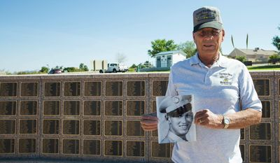 ADVANCE FOR RELEASE SUNDAY, JULY 16, 2017 AND THEREAFTER - In this Friday, July 7, 2017 photo, Hubert Gay, son of a World War II veteran who is seeking a posthumous Purple Heart award for his father, George Hubert Gay, poses in front of the Veterans Memorial with a photo of his father in Las Cruces, N.M. (Josh Bachman/The Las Cruces Sun-News via AP)