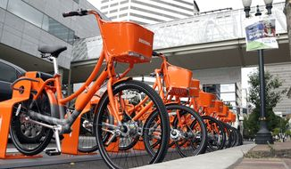 Bicycles stand at the ready for use in a bike-sharing program in Portland, Ore., Tuesday, July 19, 2016. One-thousand bikes will be available for a fee after the system goes online Tuesday with bikes located at orange-colored racks throughout much of the city. The Nike-sponsored program, called Biketown, is taking off three years later than what city leaders originally envisioned. (AP Photo/Don Ryan)