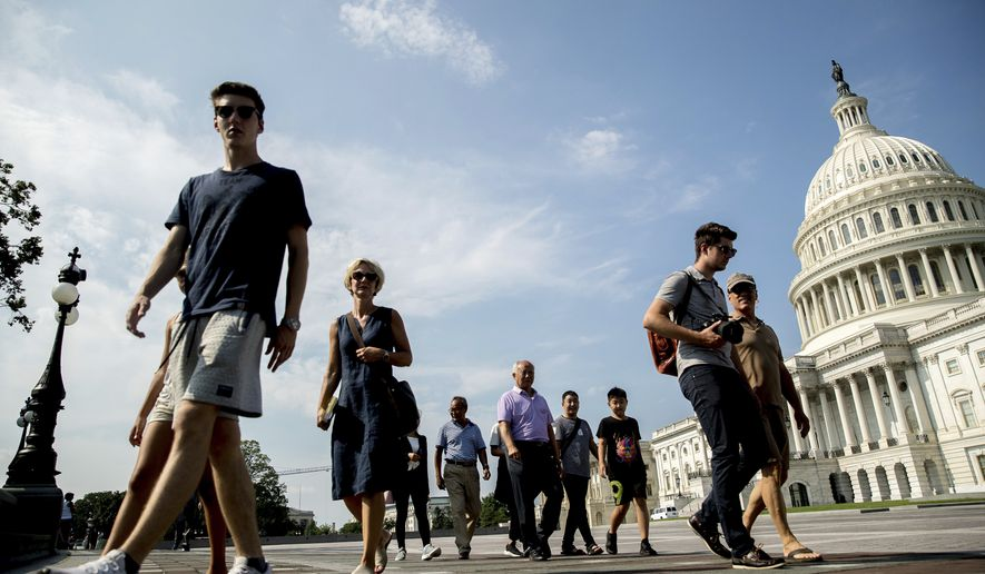 Tourists walks past the Capitol Building in Washington, Monday, July 17, 2017. The Senate has been forced to put the republican's health care bill on hold for as much as two weeks until Sen. John McCain, R-Ariz., can return from surgery. (AP Photo/Andrew Harnik)