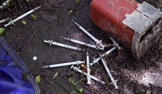 This Wednesday, June 7, 2017 photo shows discarded used hypodermic needles without protective sheaths at an encampment where opioid addicts shoot up along the Merrimack River in Lowell, Mass. Syringes left by drug users amid the heroin crisis are turning up everywhere. They hide in weeds along hiking trails and in playground grass, get washed into rivers and onto beaches, and lie scattered about in baseball dugouts and on sidewalks and streets. There are reports of children finding them and getting poked. (AP Photo/Charles Krupa)