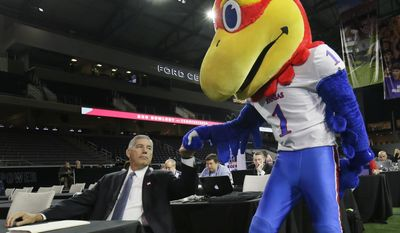 Big 12 commissioner Bob Bowlsby fist bumps the Kansas Jayhawks mascot before speaking to reporters during the Big 12 NCAA college football media day in Frisco, Texas, Monday, July 17, 2017. (AP Photo/LM Otero) ** FILE **