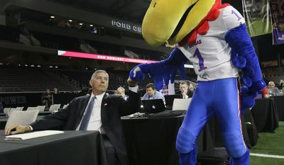 Big 12 commissioner Bob Bowlsby fist bumps the Kansas Jayhawks mascot before speaking to reporters during the Big 12 NCAA college football media day in Frisco, Texas, Monday, July 17, 2017. (AP Photo/LM Otero)