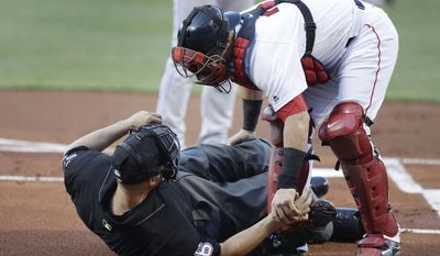Boston Red Sox catcher Christian Vazquez aids home plate umpire Chris Segal after he was accidentally hit on the head by Toronto Blue Jays' Josh Donaldson's bat during the first inning of a baseball game at Fenway Park in Boston, Monday, July 17, 2017.( AP Photo/Charles Krupa)