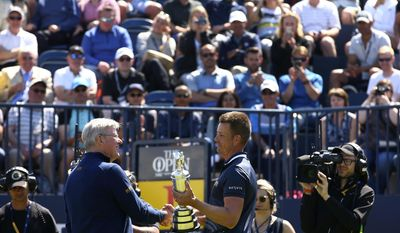 Defending champion Henrik Stenson of Sweden, right, hands over the Claret Jug to Martin Slumbers, Chief Executive of the R&A, during the second practice day at the British Open Golf Championship at Royal Birkdale in Southport, England, Monday, July 17, 2017. (AP Photo/Dave Thompson)