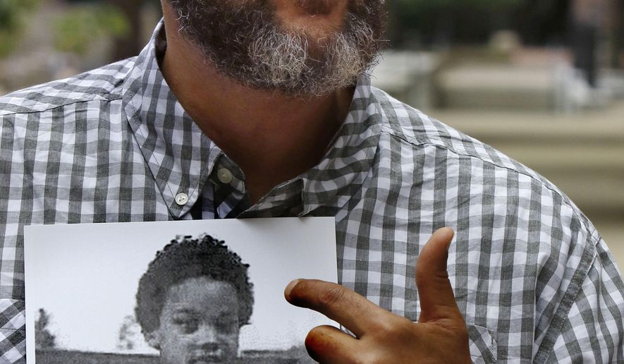 Andre Jones of New York, speaks outside the Suffolk County Courthouse Monday, July 17, 2017, in Boston after a lawsuit was filed on his behalf against the Roman Catholic Archdiocese of Boston. He holds a photo of himself when he was 8 years old. The suit alleges Jones was sexually abused as a child by the late Brother Edward Anthony Holmes, a deceased convicted pedophile who was a supervisor at Nazareth Child Care Center where Jones said he lived from 1975 to 1978, starting when he was 8 years old. (AP Photo/Bill Sikes)