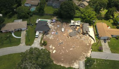 FILE-In this Friday, July 14, 2017 aerial file photo, debris is strewn about after a sinkhole damaged two homes in Land O' Lakes, Fla.  Heavy equipment will be brought in Wednesday, July 19, 2017 to the neighborhood in Pasco County, north of Tampa, to clean up debris left over from the damage caused by  the sinkhole. (Luis Santana/Tampa Bay Times via AP, File)