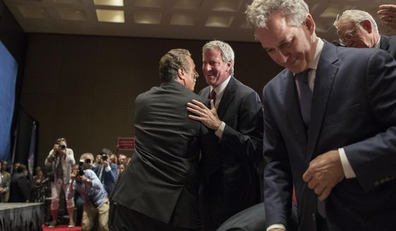New York Governor Andrew Cuomo, left, and New York City Mayor Bill de Blasio, center, hug after Cuomo spoke during a rally in support of the Affordable Care Act and against the Senate replacement bill, Monday, July 17, 2017, in New York. (AP Photo/Mary Altaffer)