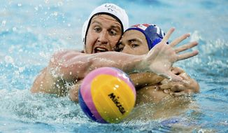 Alex Roelse of the US, left, vies for the ball with Ivan Krapic of Croatia during their men's water polo Group D preliminary round match at the 17th FINA Swimming World Championships in Hajos Alfred National Swimming Pool in Budapest, Hungary, Monday, July 17, 2017. (Szilard Koszticsak/MTI via AP)