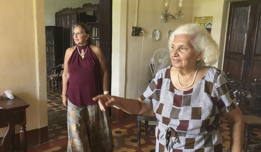 In this Friday June 2, 2017 photo, Maria de Lourdes Figueiredo de Albuquerque, 87, right, and her daughter Maria de Fatima Figueiredo de Albuquerque walk in one of the rooms of their 427-year-old Portuguese heritage home in Goa, India. The home is a much-loved and lived-in repository of memories tracing to when what is now the west-coast Indian state of Goa was a Portuguese colony. Far from the party beaches and liquor shacks that Goa has become known for, the mansion is now open as both a homestay and a museum, filled with antique furniture and artifacts from the 17th century. (AP Photo/Manish Mehta)