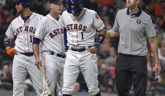 Houston Astros' Carlos Correa (1) walks off the field with manager AJ Hinch, second from left, after an injury during the fourth inning of the team's baseball game against the Seattle Mariners, Monday, July 17, 2017, in Houston. (AP Photo/Eric Christian Smith)