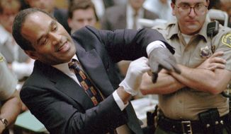FILE - In this June 15, 1995 file photo, O.J. Simpson, left, grimaces as he tries on one of the leather gloves prosecutors say he wore the night his ex-wife Nicole Brown Simpson and Ron Goldman were murdered in a Los Angeles courtroom. Simpson, the former football star, TV pitchman and now Nevada prison inmate, will have a lot going for him when he appears before state parole board members Thursday, July 20, 2017, seeking his release after more than eight years for an ill-fated bid to retrieve sports memorabilia. (AP Photo/Sam Mircovich, Pool, file)