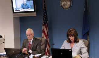 FILE - In this July 25, 2013 file photo, O.J. Simpson, in custody at the Lovelock Correctional Center, is shown on the video screen above Nevada Board of Parole hearing representative Robin Bates, left, and Commissioner Susan Jackson during a video conference parole hearing in Carson City, Nev. Simpson could have a good chance at parole when he asks officials Thursday, July20, 2017, to let him out of a Nevada prison after serving more than eight years for an ill-fated bid to retrieve sports memorabilia.  (Geoff Dornan/Nevada Appeal via AP, file)