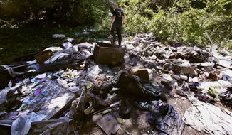 In this Wednesday June 7, 2017 photo, activist Rocky Morrison walks through an encampment where opioid addicts shoot up along the Merrimack River in Lowell, Mass. Morrison leads a cleanup effort along the Merrimack River, which winds through the old milling city of Lowell, and has recovered hundreds of needles in abandoned homeless camps that dot the banks, as well as in piles of debris that collect in floating booms he recently started setting. (AP Photo/Charles Krupa)
