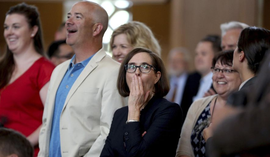 Gov. Kate Brown reacts to a moment in a video played after the House of Representatives enacted Sine Die to adjourn the legislative session at the state Capitol in Salem, Ore. on Friday, July 7, 2017. The Oregon Legislature has adjourned the 2017 session that saw the passage of record-funding for schools, a long-term transportation package, gun restrictions, cost-free abortions and health care funding for Medicaid and undocumented immigrants. (Anna Reed/Statesman-Journal via AP)