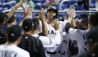 Miami Marlins' Giancarlo Stanton is congratulated by teammates after hitting a two-run home run during the first inning against the Philadelphia Phillies in a baseball game Monday, July 17, 2017, in Miami. (AP Photo/Wilfredo Lee)