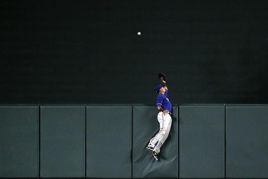 Texas Rangers center fielder Carlos Gomez leaps as a solo home run by Baltimore Orioles' Seth Smith sails over the outfield wall during the seventh inning of a baseball game in Baltimore, Monday, July 17, 2017. Baltimore won 3-1. (AP Photo/Patrick Semansky)