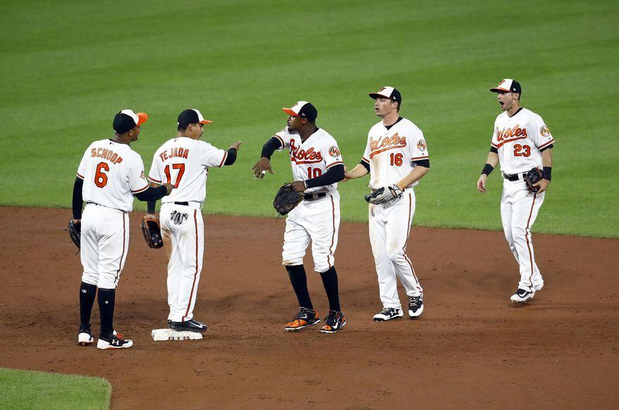 Baltimore Orioles' Jonathan Schoop, Ruben Tejada, Adam Jones, Trey Mancini and Joey Rickard, from left, celebrate after the team's baseball game against the Texas Rangers in Baltimore, Monday, July 17, 2017. Baltimore won 3-1. (AP Photo/Patrick Semansky)