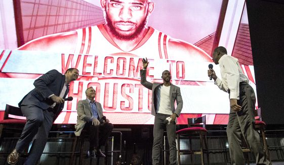 Chris Paul waves to fans after being introduced as the newest member of the Houston Rockets Friday, July 14, 2017, in Houston. The nine-time All-Star was traded from the Los Angeles Clippers late last month. Joining Paul on stage, from left to right, are Rockets announcer Craig Ackerman, coach Mike D'Antoni and basket hall of fame member Calvin Murphy. (AP Photo/David J. Phillip)