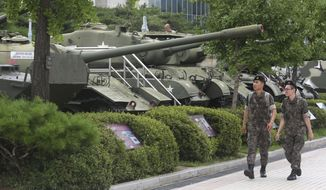 South Korean army soldiers pass by military vehicles deployed in the Korean War era at Korea War Memorial Museum in Seoul, South Korea, Monday, July 17, 2017. South Korea offered Monday to talk with North Korea to ease animosities along their tense border and resume reunions of families separated by their war in the 1950s. (AP Photo/Ahn Young-joon)