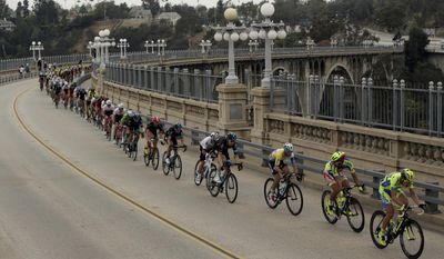 FILE - In this May 17, 2015, file photo, bicyclists cross the Colorado Street Bridge on the final stage of the Amgen Tour of California cycling in Pasadena, Calif. Citing an increase in suicide attempts, officials are installing temporary fencing on the famous Los Angeles-area bridge to prevent people from climbing over the side.  The city council is expected to discuss a more permanent solution at a meeting Wednesday, July 19, 2017. (AP Photo/Damian Dovarganes, File)
