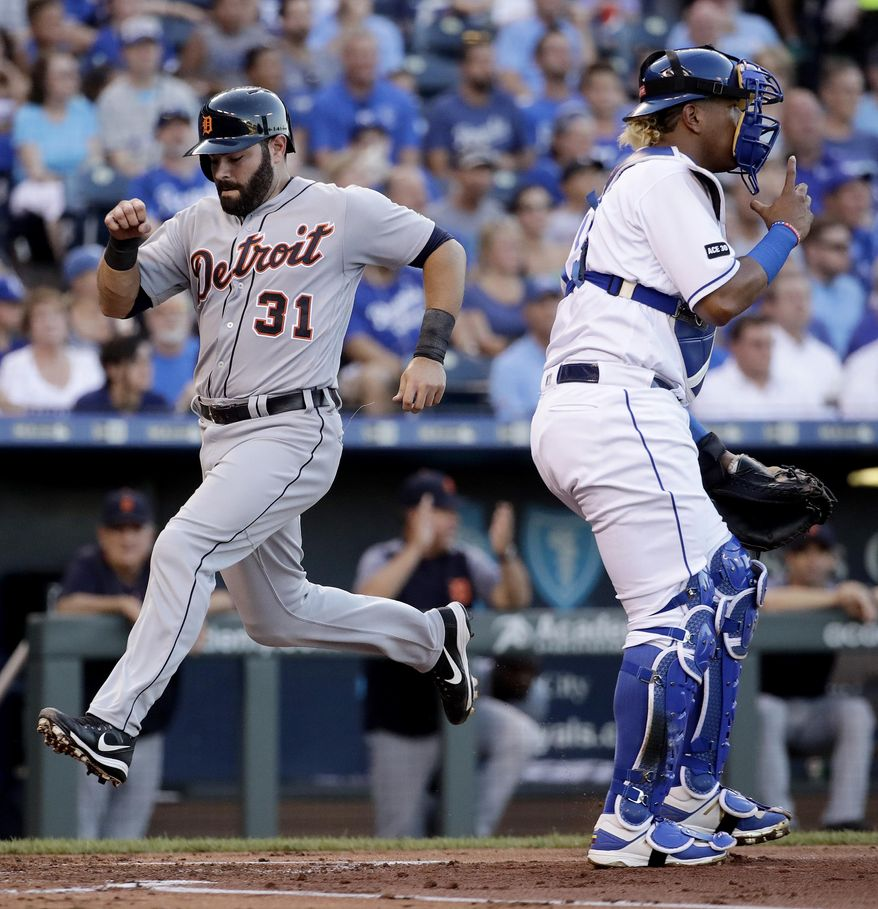 Detroit Tigers' Alex Avila (31) crosses the plate past Kansas City Royals catcher Salvador Perez to score during the second inning of a baseball game Monday, July 17, 2017, in Kansas City, Mo. (AP Photo/Charlie Riedel)