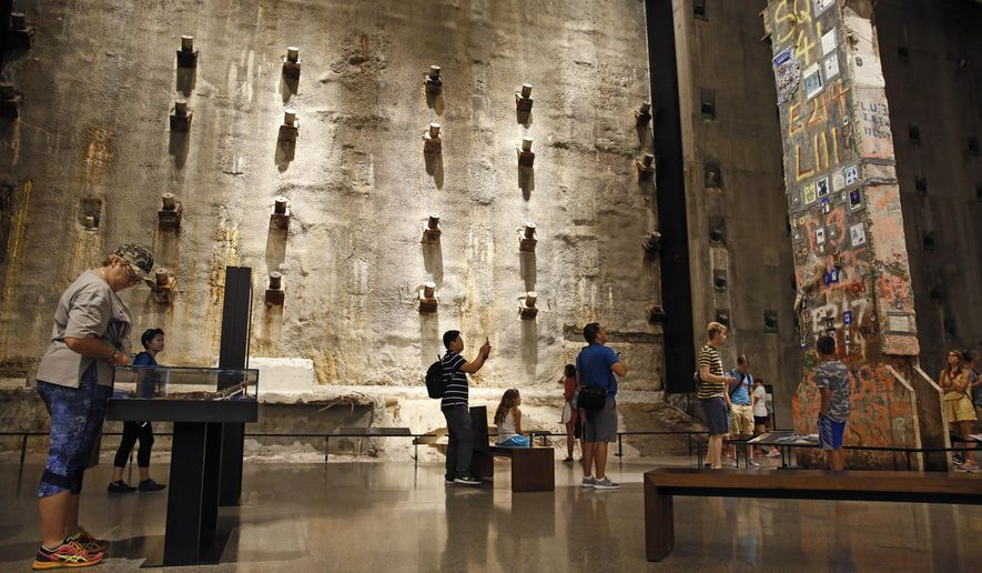 "In this July 11, 2017, photo, visitors to the Foundation Hall at the National September 11 Memorial and Museum view the slurry wall, rear, and a beam from one of the World Trade towers, right, that was preserved by rescue and recovery workers at the site in New York. Last winter the U.S. tourism industry worried about a ""Trump slump,"" fearing that Trump administration policies might discourage international travelers from visiting the U.S. But statistics from the first half of 2017 suggest that the travel to the U.S. is robust and a number of sectors have reported increased international visitation, with one expert calling it a ""Trump bump.""  (AP Photo/Kathy Willens)"