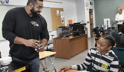 IMAGE DISTRIBUTED FOR TEXAS INSTRUMENTS - Baltimore Ravens lineman and math scholar John Urschel, left, hands out ice cream to Chelsy Valerio, 14, of Baltimore, during a STEM lesson at Dundalk High School during the launch of Texas Instruments' STEM Behind Cool Careers series on Tuesday, July 18, 2017 in Baltimore. The fun, free activities show students how a solid understanding of STEM subjects is vital for any career, even careers students least expect. (Steve Ruark/AP Images for Texas Instruments)