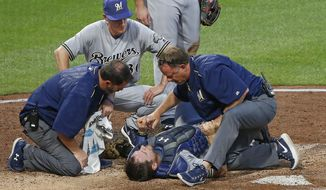 Milwaukee Brewers manager Craig Counsell, top, watches as team trainers examine catcher Stephen Vogt, who was injured in a collision with Pittsburgh Pirates' Chad Kuhl, who was out attempting to score in the fifth inning of a baseball game in Pittsburgh, Monday, July 17, 2017. Both players were shaken up on the play and Vogt left the game. (AP Photo/Gene J. Puskar)