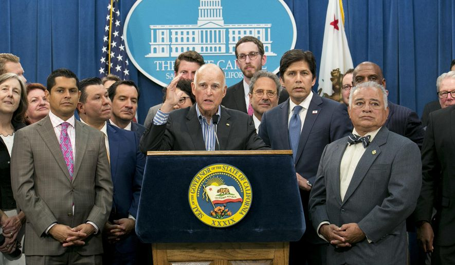 Gov. Jerry Brown, center, flanked by lawmakers from both sides of the aisle, speaks of the passage of a pair of climate change measures, Monday, July 17, 2017, in Sacramento, Calif.(AP Photo/Rich Pedroncelli)