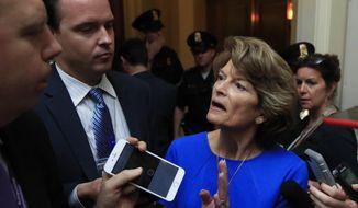 Sen. Lisa Murkowski, R-Alaska, is surrounded by reporters as she walks toward the Senate floor on Capitol Hill in Washington, Tuesday, July 18, 2017. (AP Photo/Manuel Balce Ceneta) ** FILE **