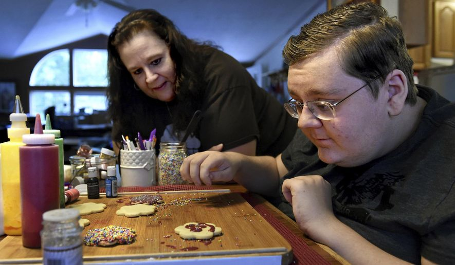 In this June 29, 2017, photo, Daniel Pooler analyzes the smiley-face sugar cookie he has just decorated with frosting and sprinkles as his mom, Julie Pooler, looks on in their home in Lake Elmo, Minn. Julie's dream is to start a baking business that teaches and employs special-needs students. It would be called Daniel's Desserts, after her 16-year-old son who has autism and epilepsy. (Jean Pieri/Pioneer Press via AP)