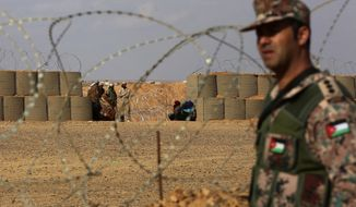 In this Feb. 14, 2017 file photo, a Jordanian soldier stands guard at the northeastern border with Syria, close to the informal Rukban camp for displaced Syrians. Desperate to help Syrians stuck on Jordan's sealed border, U.N. agencies reluctantly agreed late last year to hand much of the control over aid distribution to Jordan's military, a Jordanian contractor and a Syrian militia. Since then, the system has broken down repeatedly and only sporadic aid shipments have reached the two remote desert camps on the border. (AP Photo/Raad Adayleh, File)
