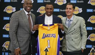 Los Angeles Lakers' Kentavious Caldwell-Pope, center, poses for photos with Magic Johnson, left, and general manager Rob Pelinka during a news conference Tuesday, July 18, 2017, in Los Angeles. (AP Photo/Jae C. Hong)