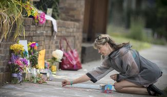Megan O'Leary, of St. Paul, leaves a message on the sidewalk near the scene where a Minneapolis police officer shot and killed Justine Damond, of Australia, Monday, July 17, 2017, in Minneapolis. Relatives and neighbors of the Australian woman fatally shot by Minneapolis police over the weekend demanded answers Monday about the mysterious shooting in which the meditation teacher was reportedly killed by an officer who fired from the passenger seat of a squad car as the woman stood outside the driver's door. (Elizabeth Flores/Star Tribune via AP)