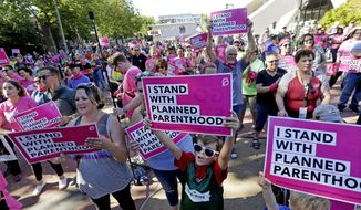 Seattle Storm fans and others cheer at a rally in support of Planned Parenthood before a WNBA basketball game between the Storm and the Chicago Sky on Tuesday, July 18, 2017, in Seattle. (AP Photo/Elaine Thompson) ** FILE **