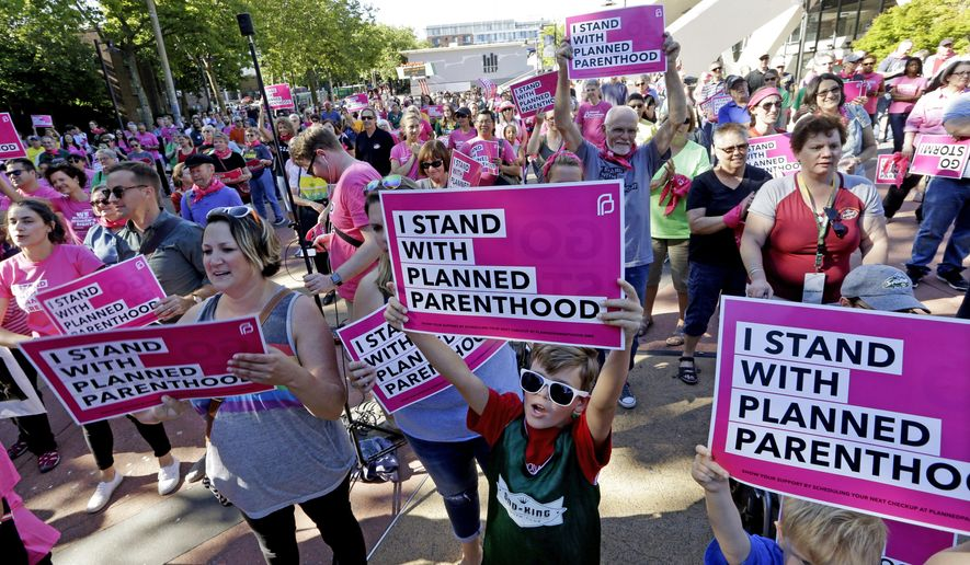 Seattle Storm fans and others cheer at a rally in support of Planned Parenthood before a WNBA basketball game between the Storm and the Chicago Sky on Tuesday, July 18, 2017, in Seattle. (AP Photo/Elaine Thompson)