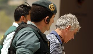Former President of the Spanish Football Federation Angel Maria Villar, right, is lead by Spanish Civil Guard policeman to enter the Federation headquarters during an anti-corruption operation in Las Rozas, outside Madrid, Tuesday, July 18, 2017.  Villar, FIFA's senior vice president and a long-time player in world soccer, was arrested Tuesday along with his son and two more federation executives in an anti-corruption investigation. (AP Photo/Francisco Seco)