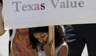 """A young girl holds a sign as protesters gather on the steps of the Texas Capitol while State lawmakers begin a special legislative session called by Republican Gov. Greg Abbott in Austin, Texas, Tuesday, July 18, 2017. Immigrant rights groups plan to increase protests of the new law that allows police to inquire about peoples' immigration status, while LGBT activists bitterly oppose """"bathroom bill"""" proposals. (AP Photo/Eric Gay)"""
